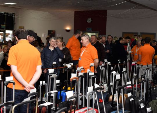 Volunteers, supporters, and bags, at the Magpas Air Ambulance unclaimed luggage auction